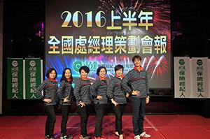 6個員工照身高排列側身以模特兒的姿勢於處經理策劃會報看板前合影