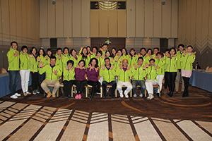 MDRT得獎員工穿綠色外套雙手張開放胸前合影