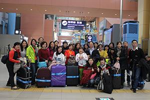 員工於機場大廳處提著行李箱合影