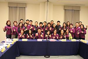 另一批員工於審查會桌前穿著紫色制服合影