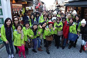部分員工穿著綠色制服外套於日本街道上合影