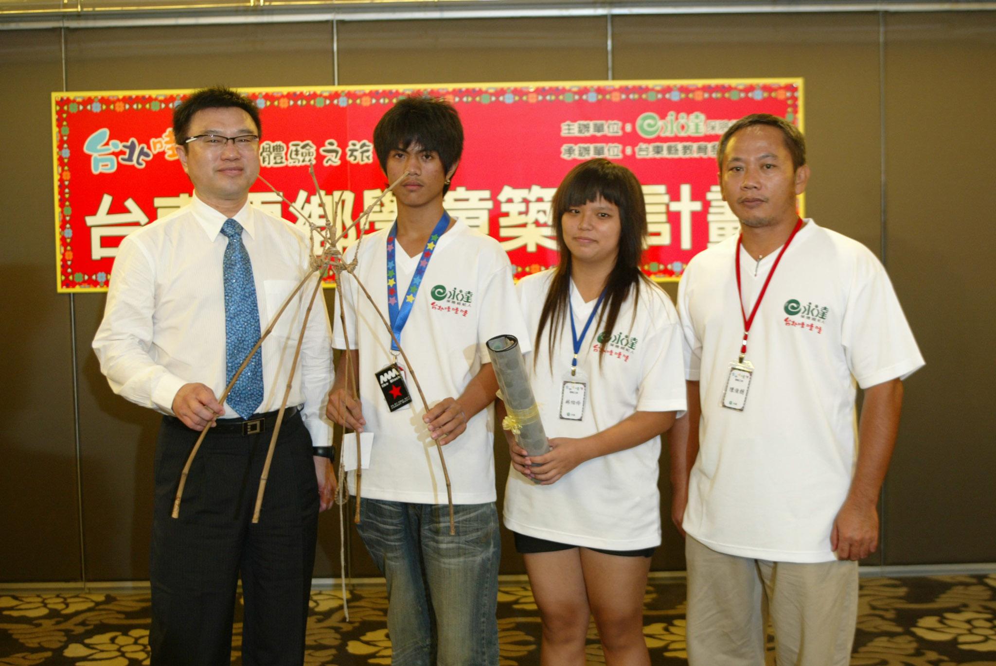 第二屆學童(圖中二名)代表致贈永達吳文永董事長(圖左一) 親手製做的贈禮。