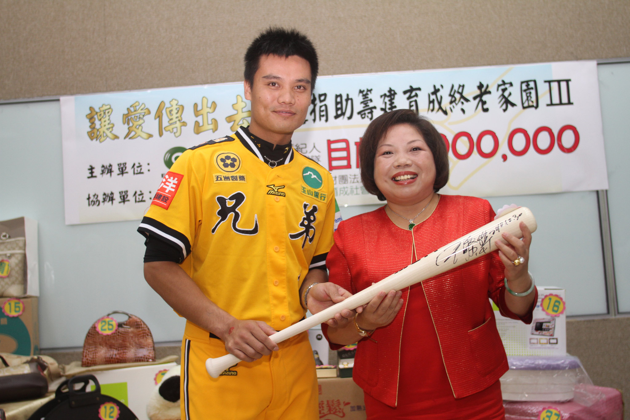 永達黃素英副總(右)高價標下兄弟象王勝偉(左)提供的專屬貼身練習球棒。