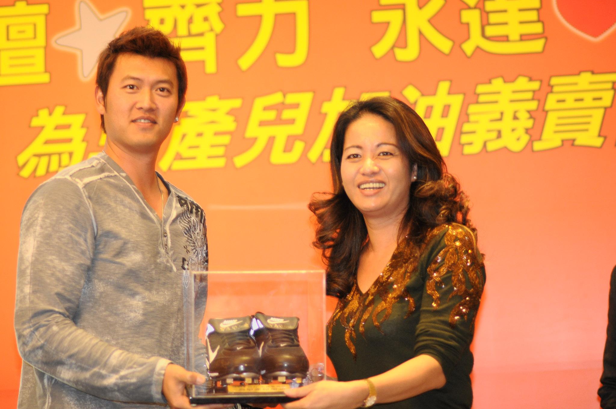 王建民(左)親筆簽名比賽釘鞋由永達保經李麗英副總(右)以12萬元得標。