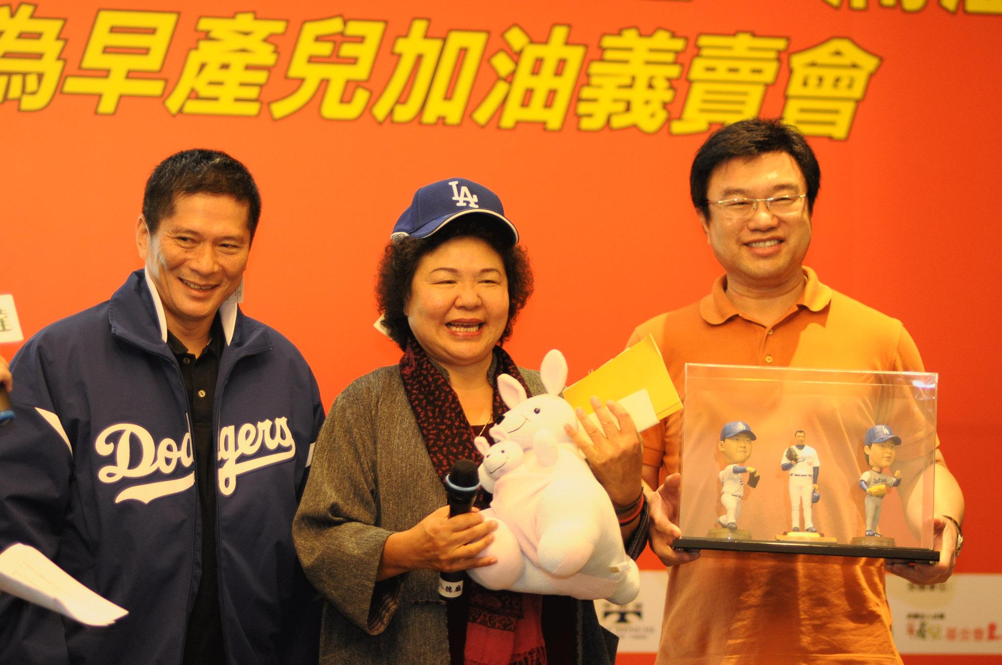 高雄市市長陳菊(中),副市長李永得(左)主拍郭泓志公仔及道奇隊夾克及帽子由永達吳文永董事長(右)以30萬元標得。