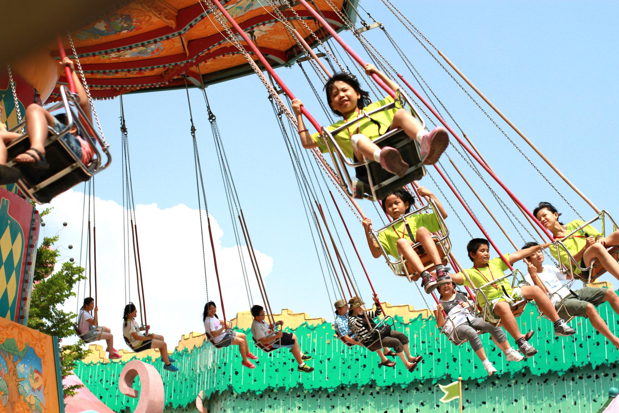 孩子們坐上從未見過的遊樂設施,臉上展露燦爛純真的笑容。