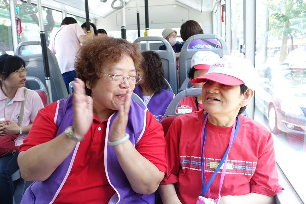 永達魏滿妹協理(圖左)與憨兒開心的在巴士上 哼哼唱唱。