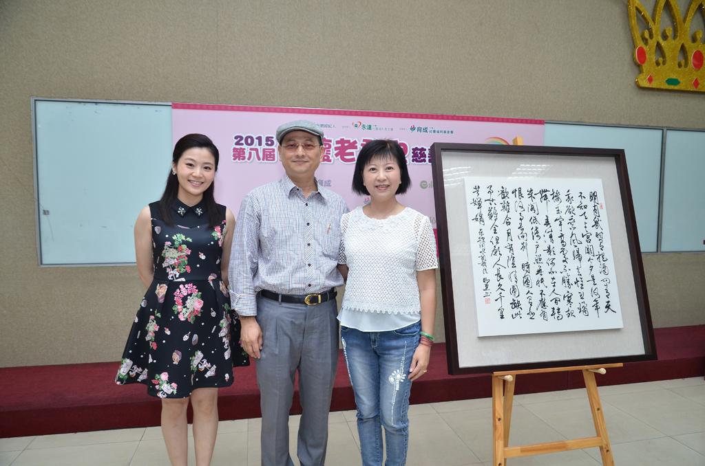 【李明堂墨寶】董事長夫婦再捐出,主持人楊小黎(左一)拍出由永達陳世卿處經理夫婦(右)20萬得標。