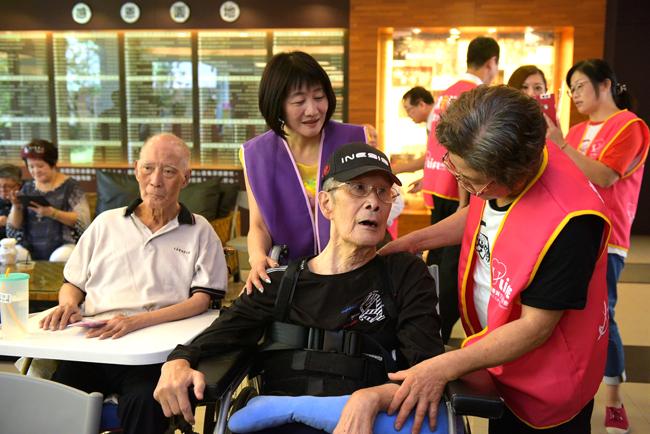 (左二)永達林佳儀協理耐心陪伴老伯伯說話聊天。