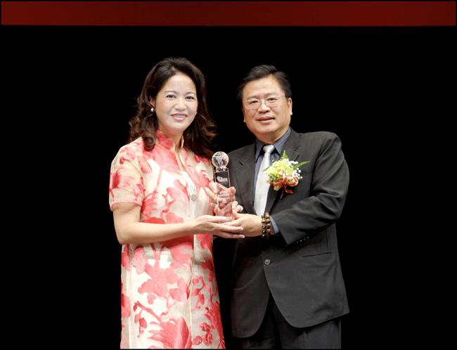 壽險公會許舒博理事長頒發「最佳社會貢獻獎」給永達保經李麗英副總。