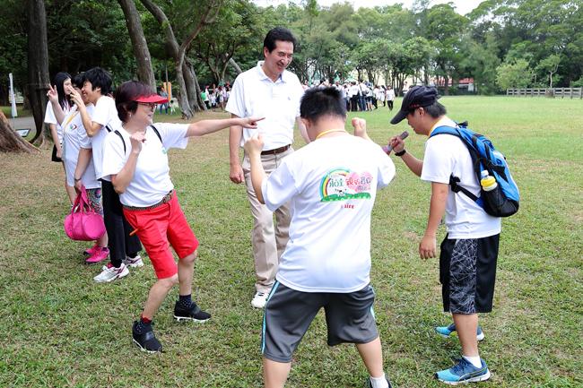 (左一)台灣優質生命協會紀寶如秘書長、永達保經陳慶鴻總經理與可愛的憨兒寶貝 愉快的在草皮上嬉戲。
