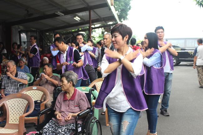 永達蔡名蔚籌備協理帶領中區志工一起進行暖身操,鼓勵機構長者多活動手腳。