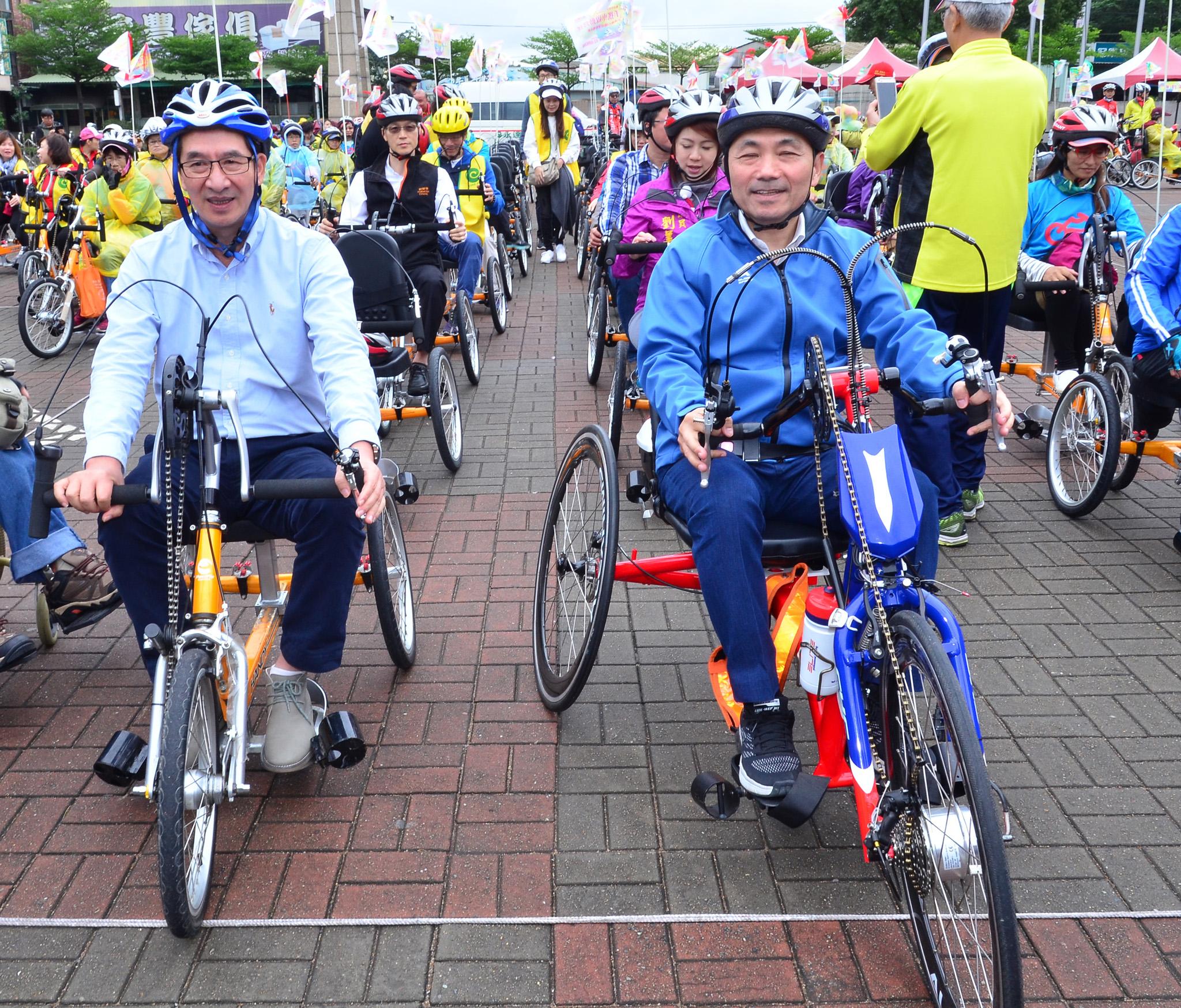 永達保經總經理陳慶鴻(左)與新北市副市長侯友宜(右)一同為板樹園區啟動營運加入手搖車領騎。