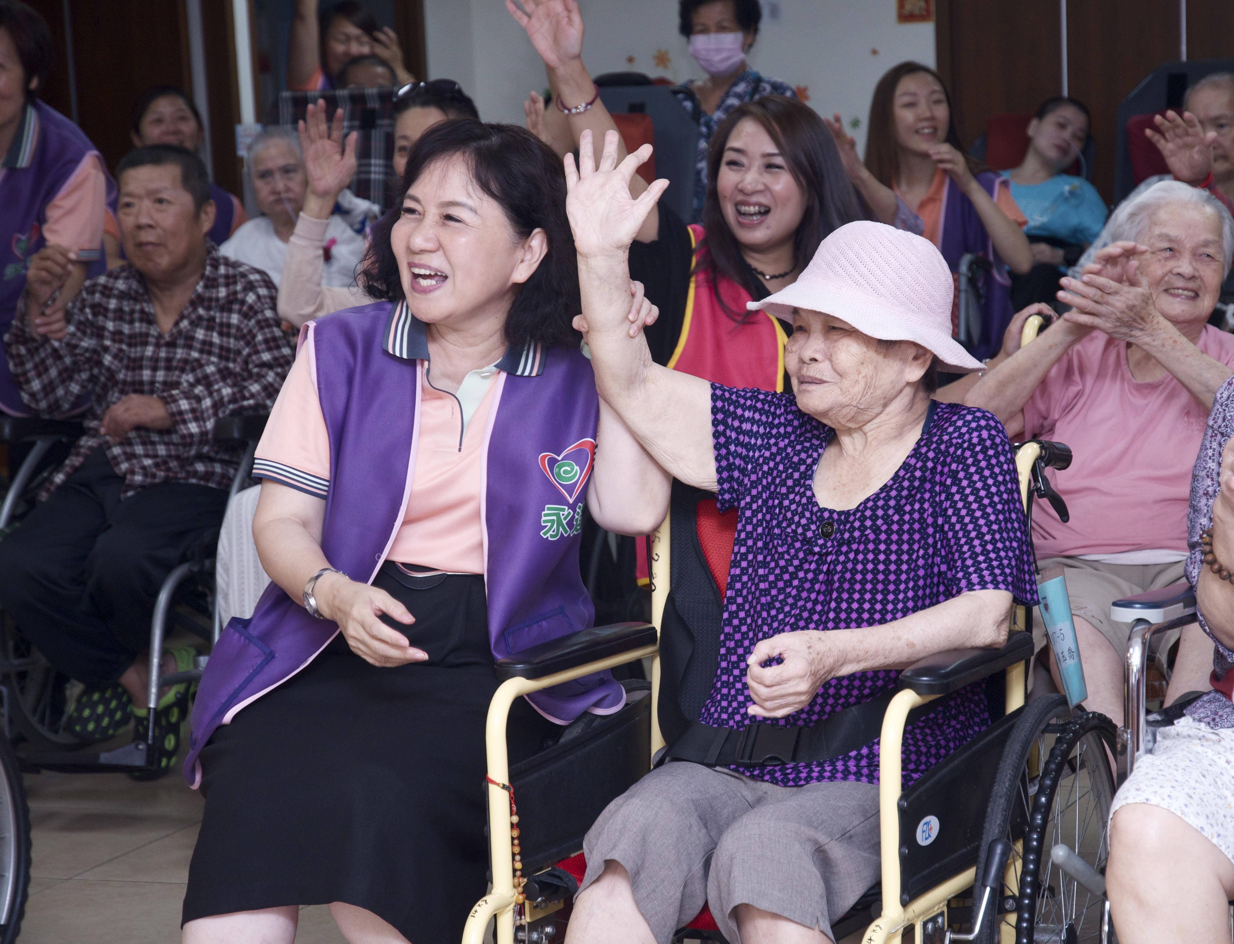 志工協助長者與台上互動搶答問題拿贈品。