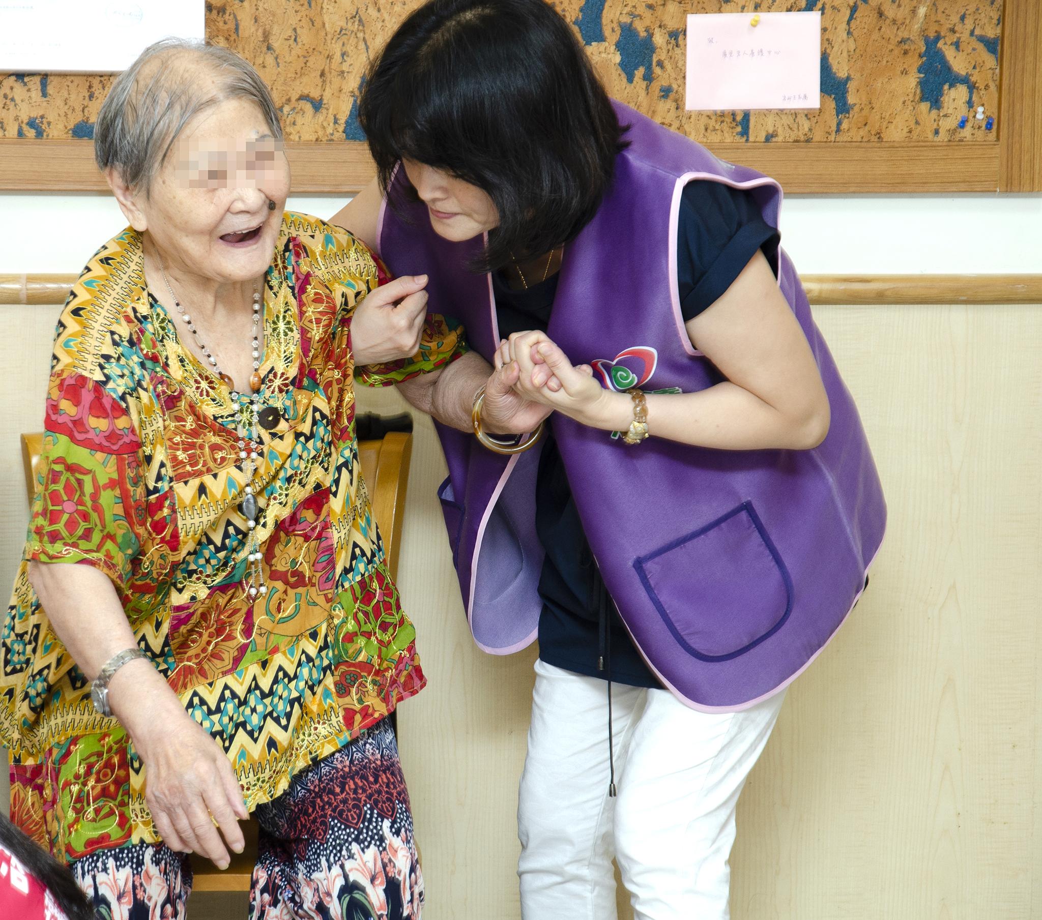 永達志工協助長輩起立。