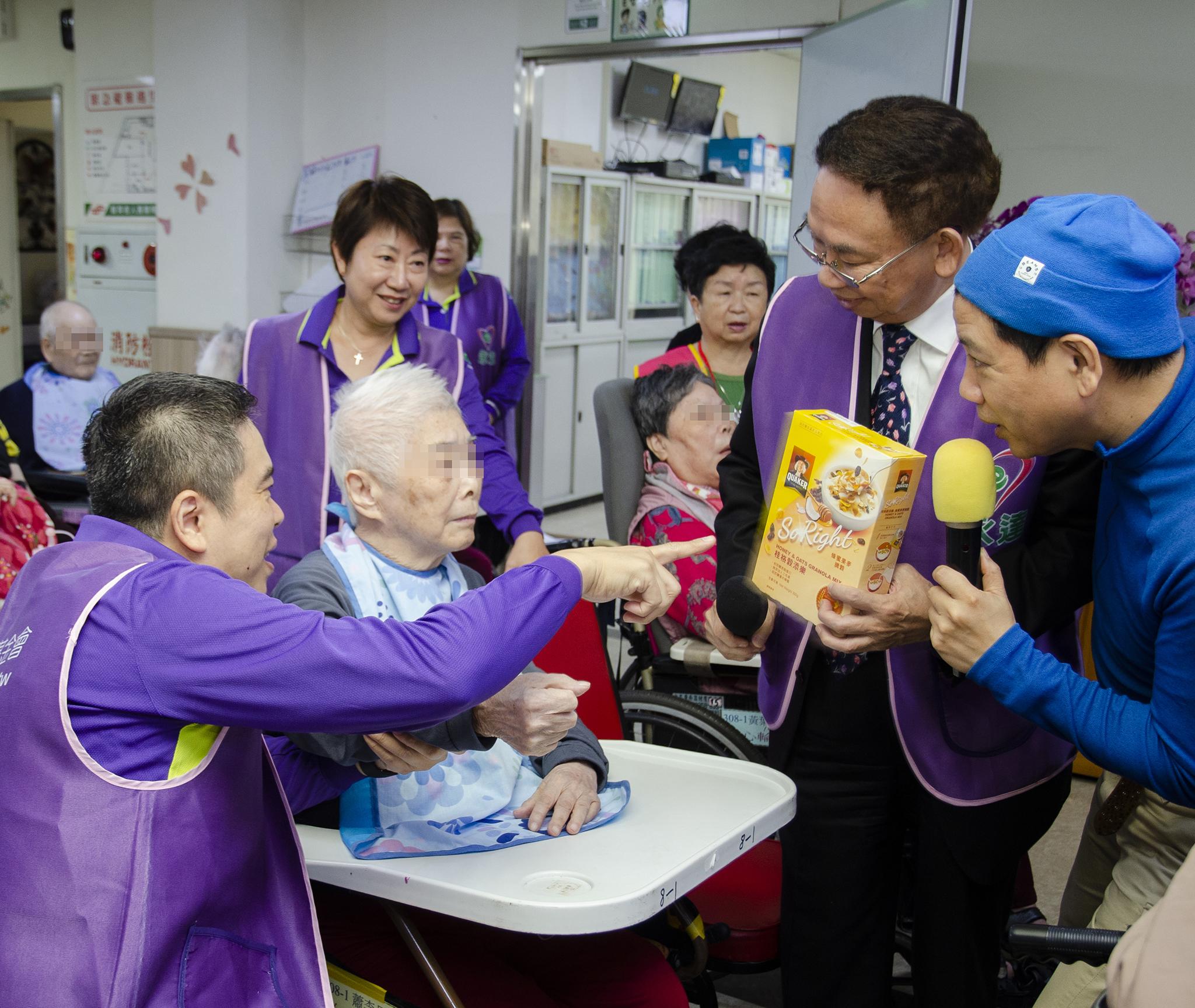 永達志工與主持人陳凱倫幫助長輩回答正確答案贏得獎品。