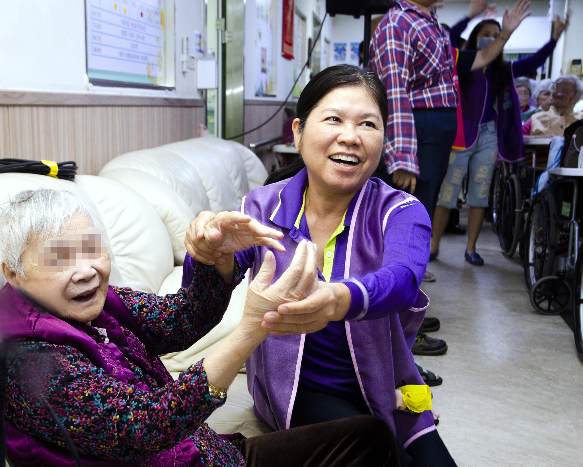 永達志工協助長輩跟著音樂舉手舞動。