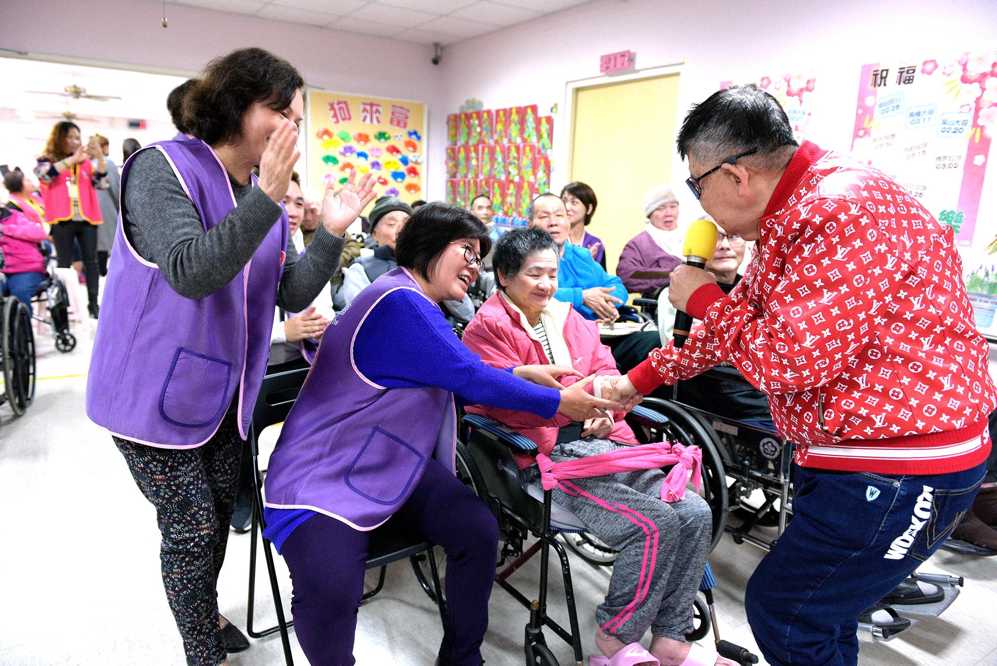 藝人和永達志工與長輩互動。