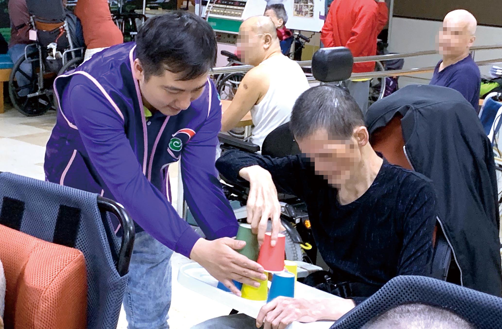 志工陪伴長輩完成「疊杯子」任務,彼此內心都充滿成就感與喜悅。