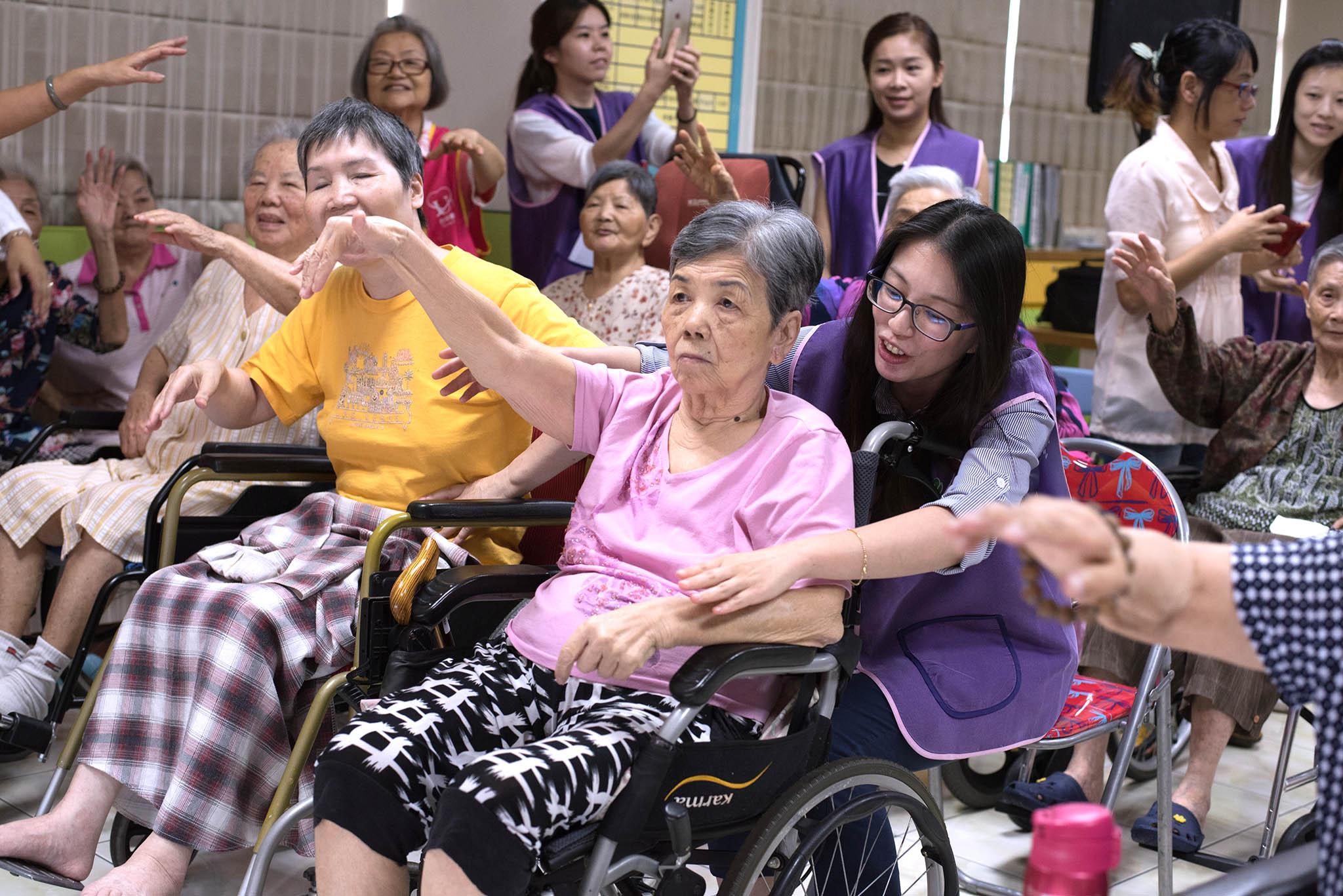 永達志工協助長輩伸展。
