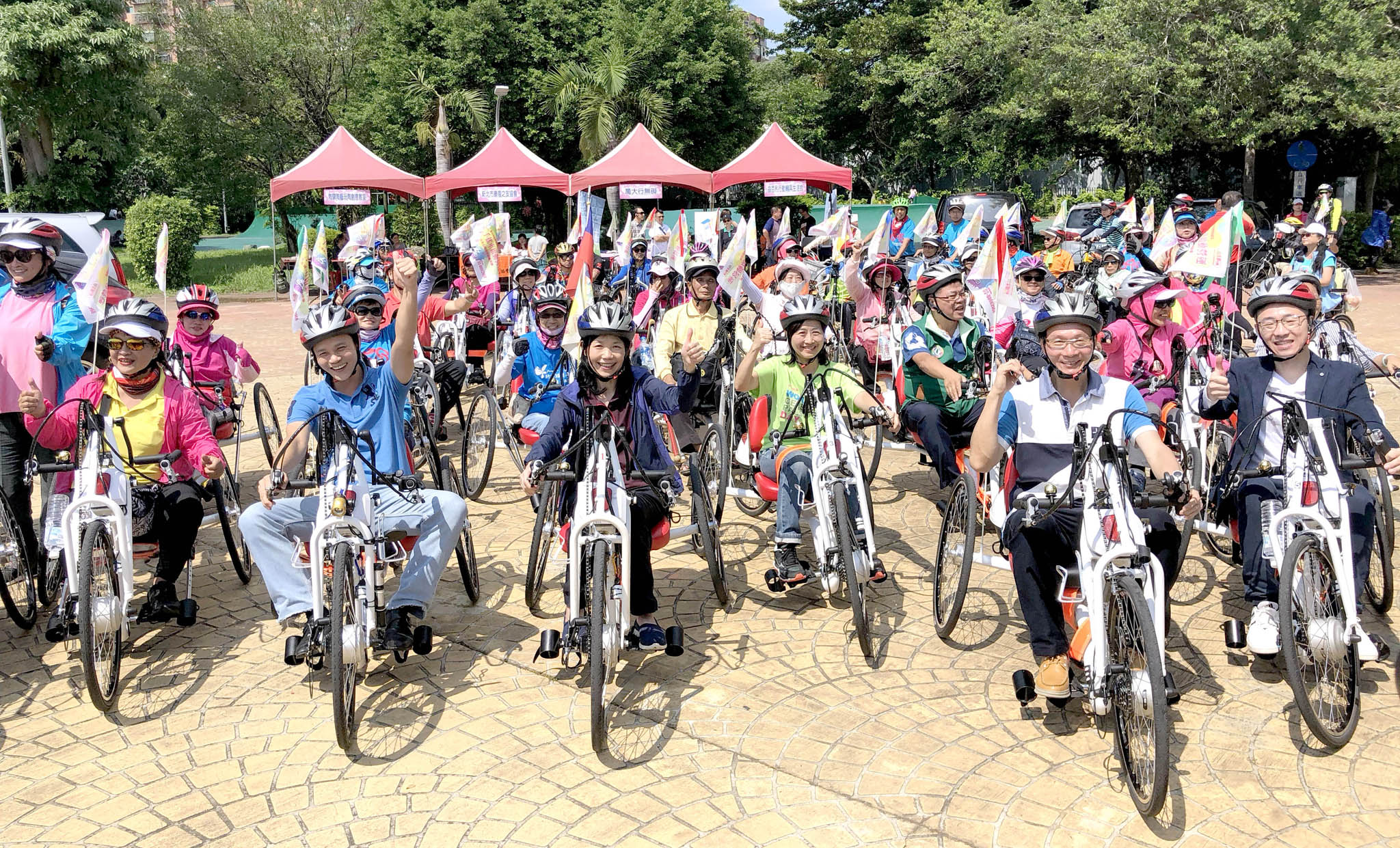 新北市呂衛青副市長(前排左三)帶領與會貴賓騎乘電輔式手搖車。