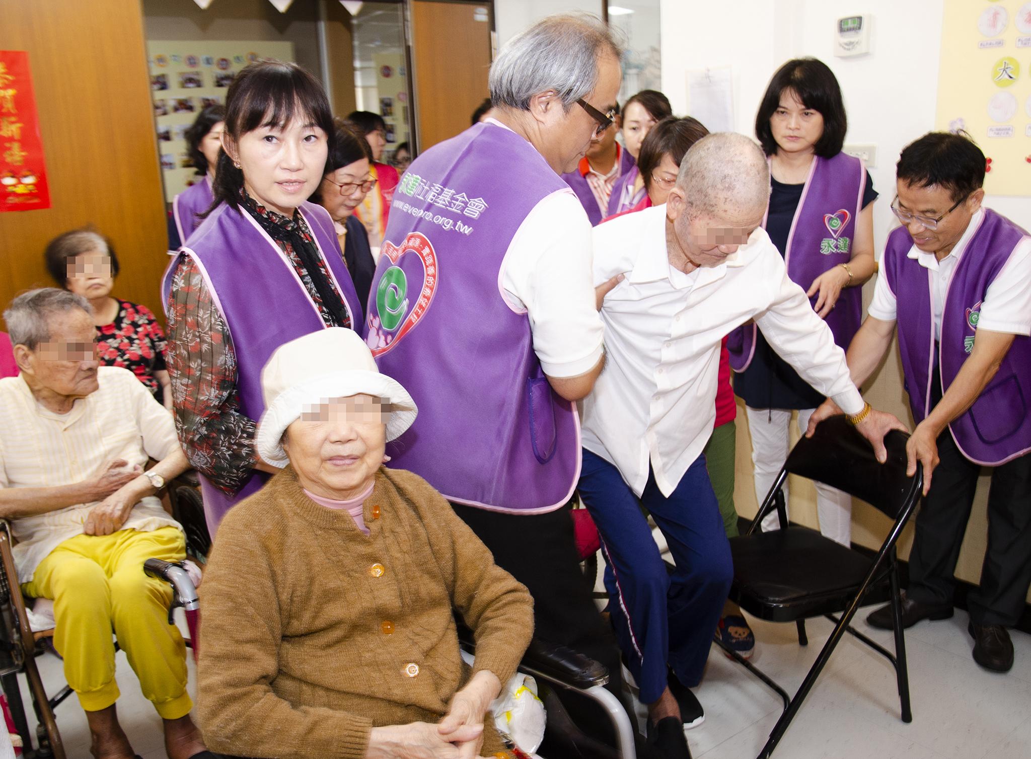 永達志工熱心協助行動不便長者入坐。