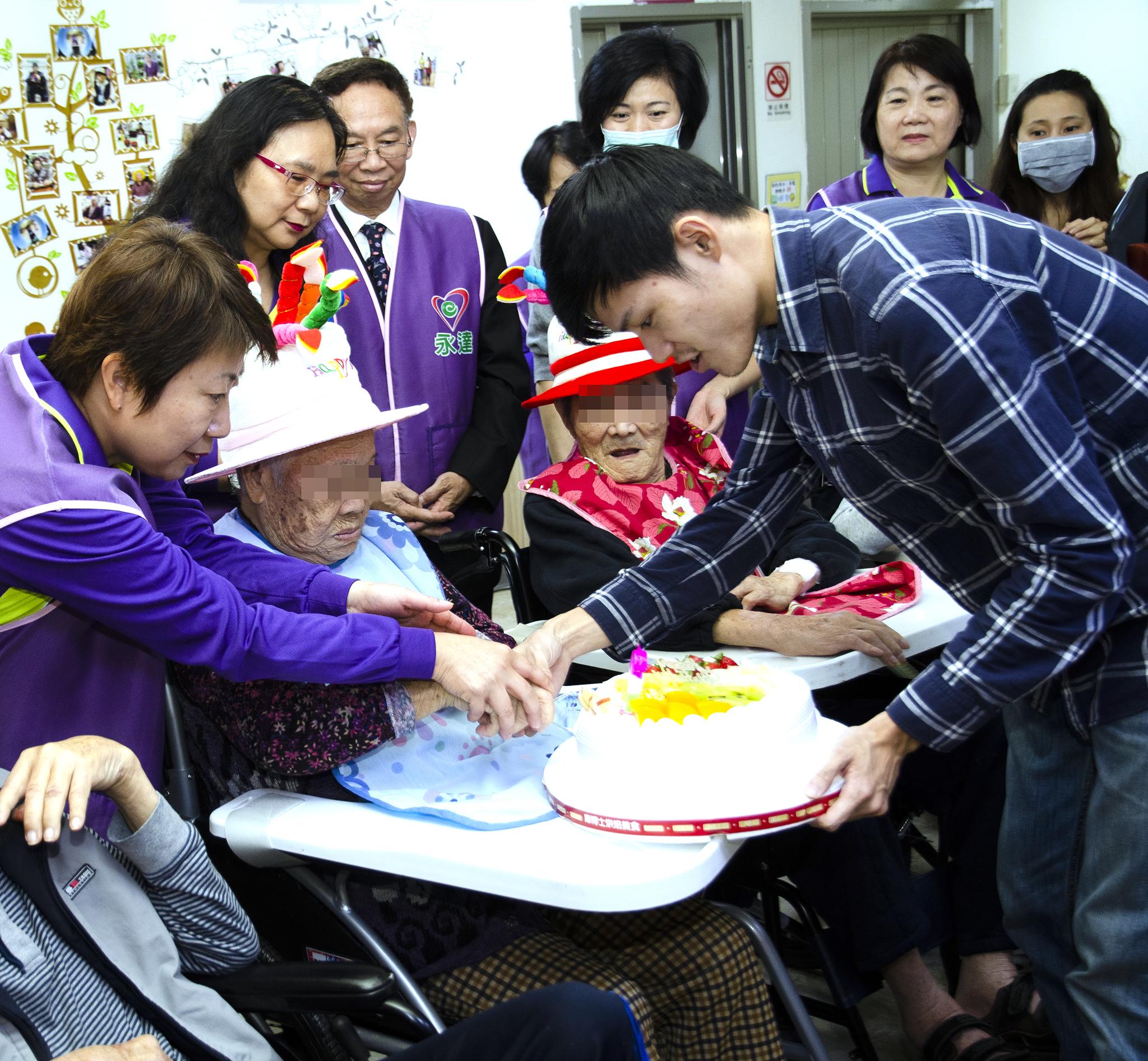 永達志工協助十二月壽星長輩切蛋糕。