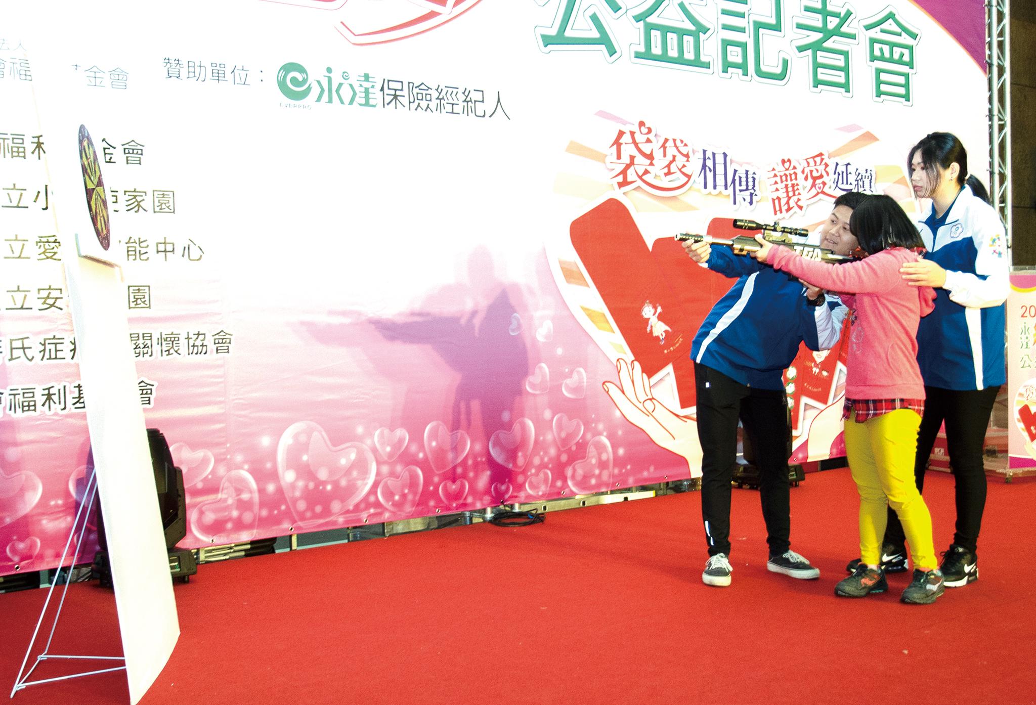 空氣槍神射手-林穎欣 (右1)、呂紹全 (左1) 教唐氏症孩子體驗射擊。