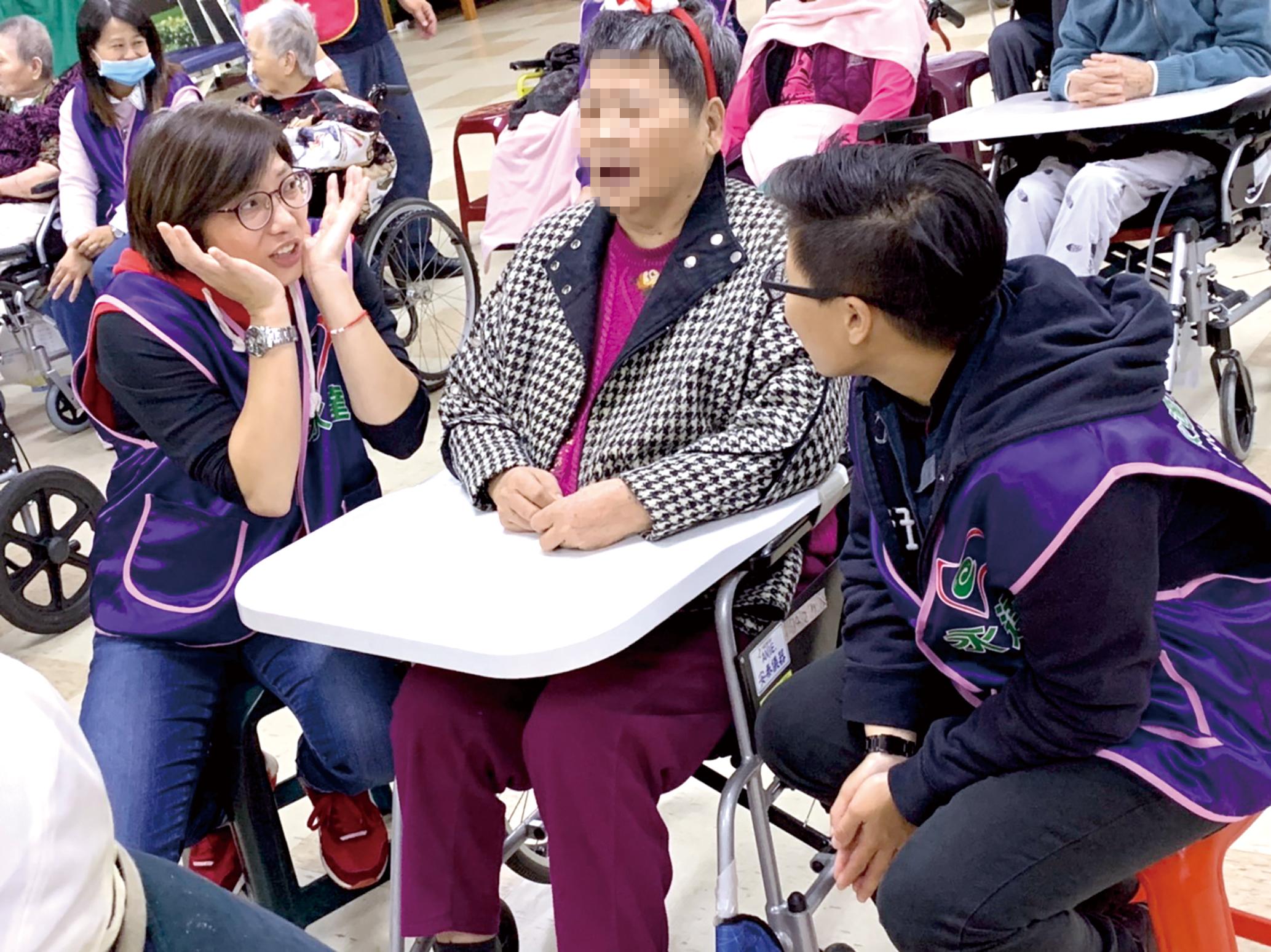 志工陪奶奶聊天,逗她開心笑。